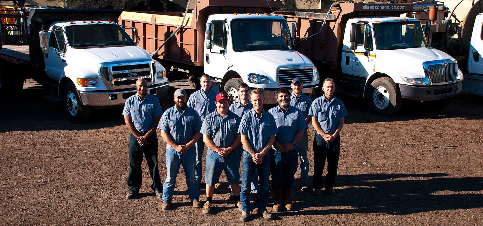 All Seasons staff with trucks